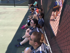 Watching mixed doubles tennis in the shade.