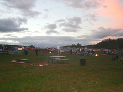 View of the picnic area with bonfires as dusk approaches.